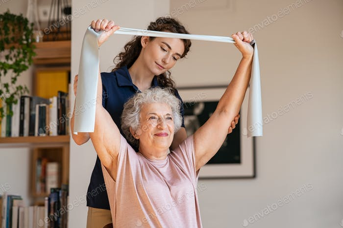 Senior patient doing exercise with elastic band at home with personal trainer