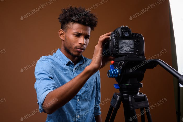Young handsome African man vlogging with DSLR camera in studio