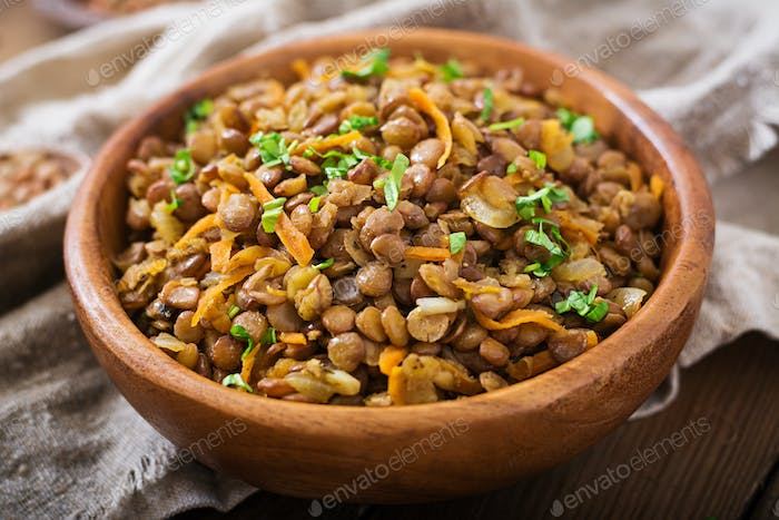 Lentil with carrot and onion in wooden bowl. Healthy lifestyle. Diet menu.