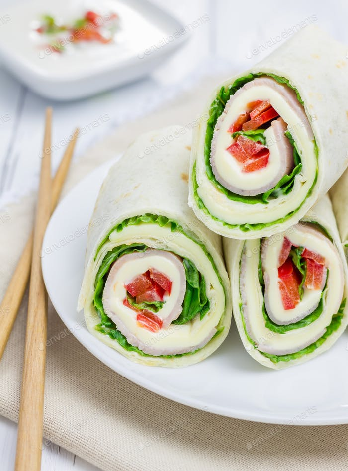 Tortilla roll with soft cheese, chicken ham, and vegetables, closeup