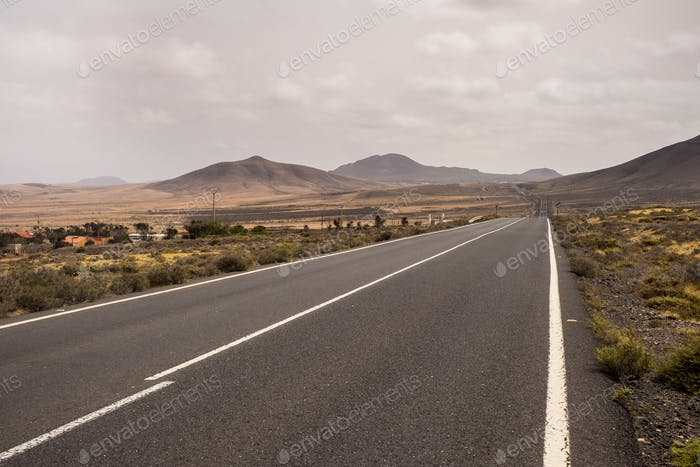 long way road from valley to mountains in the middle of nothing