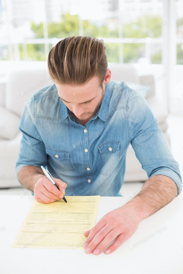 Young businessman signing a contract in his office