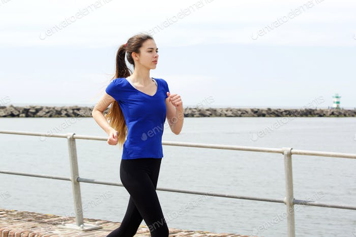 Young sporty woman training by the sea