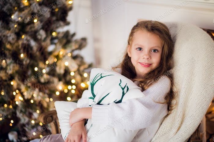 girl at Christmas, xmas tree in the background, beautiful young kid wrapped in a blanket, she smiles