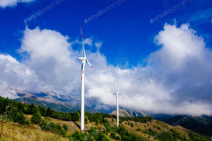 Aerial view of wind turbine farm. Wind power plants in green summer landscape with clouds.