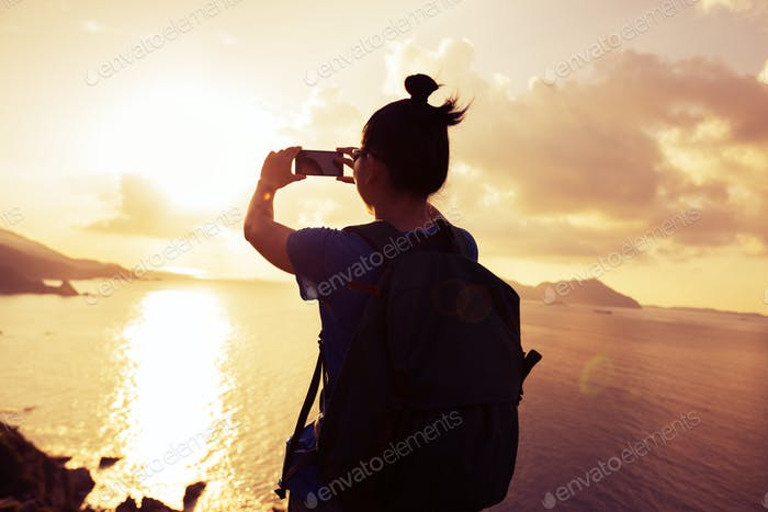 Woman taking photo with mobile phone on sunrise seaside