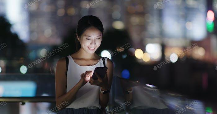 Frau Nutzung des Mobiltelefons in der Stadt in der Nacht