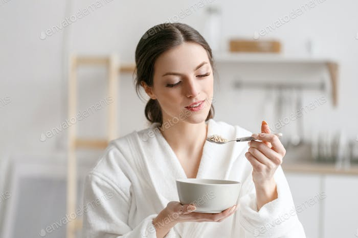 Woman eat in kitchen, woman with bowl breakfast home morning