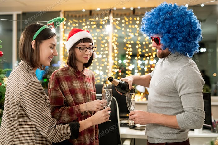 Group of businesspeople celebrating Christmas in office and having champagne