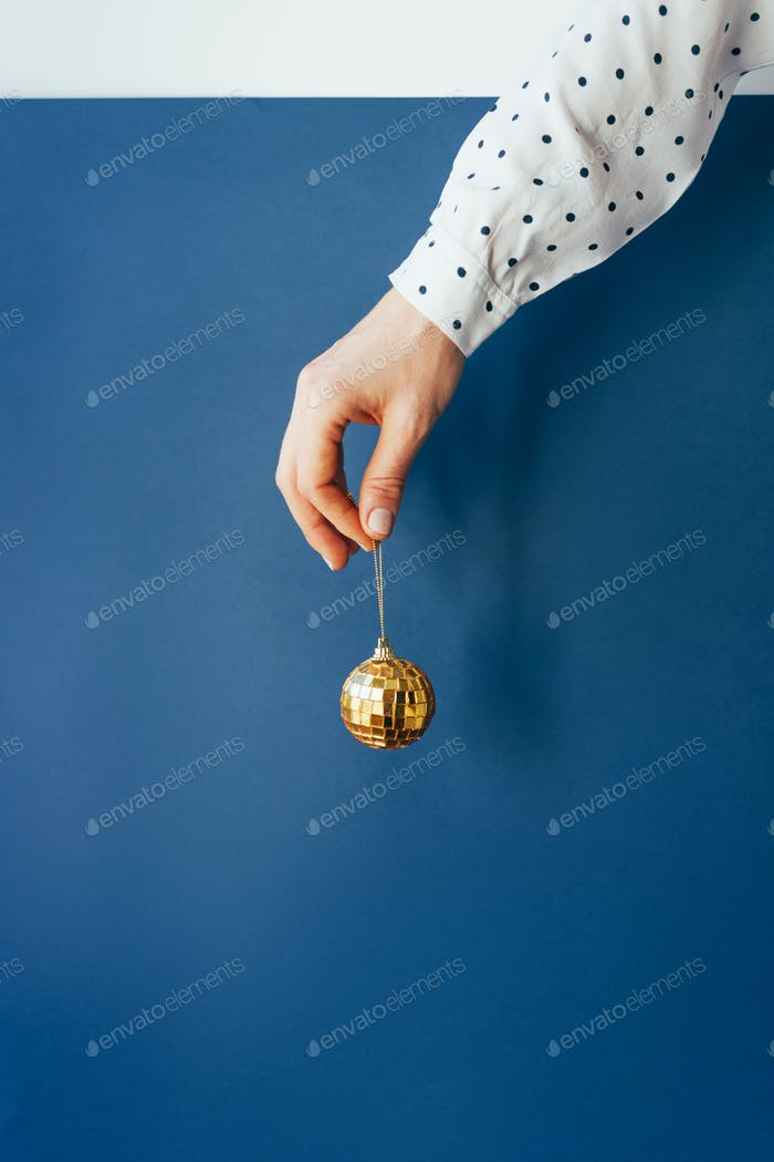 A woman's hand in a polka-dot shirt holds a golden sparkling Christmas ball on a blue background.