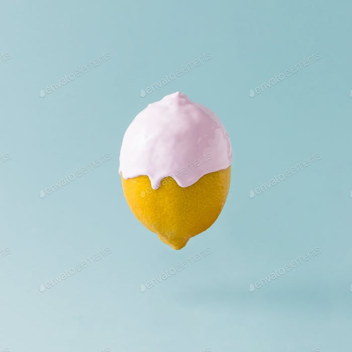 Lemon with ice cream topping on pastel blue background. Food creative concept.
