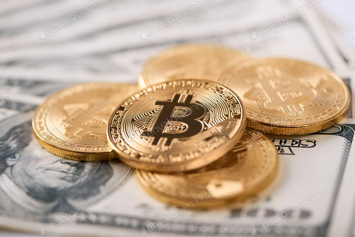 Encrypted golden bitcoins lying on old hundred dollar banknotes
