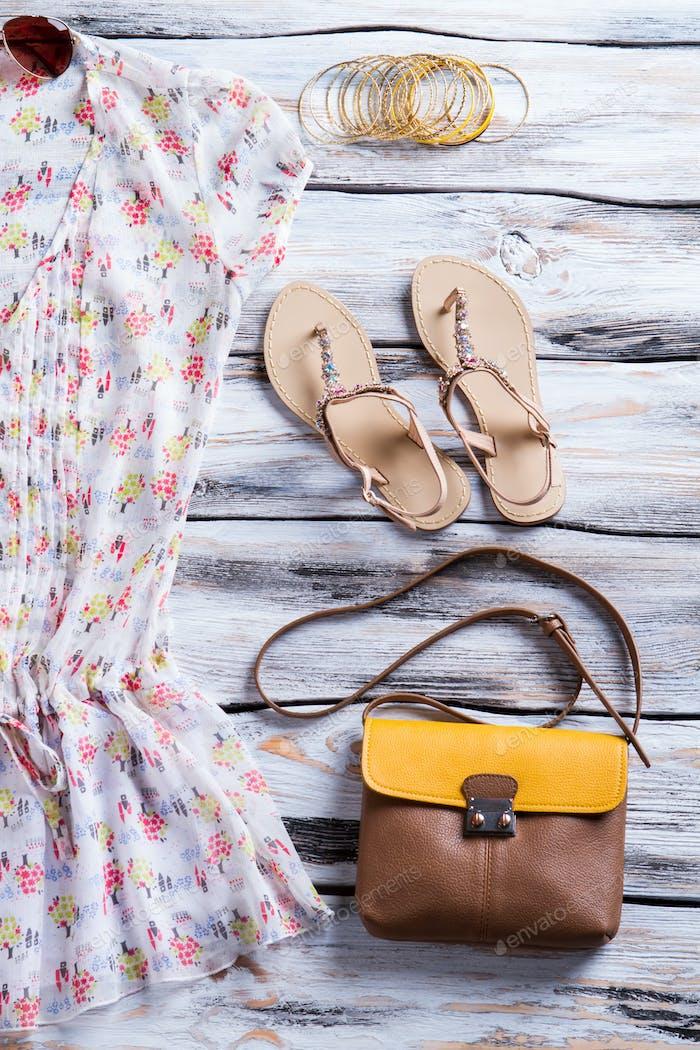 Bluse und Geldbörse mit Sandalen.
