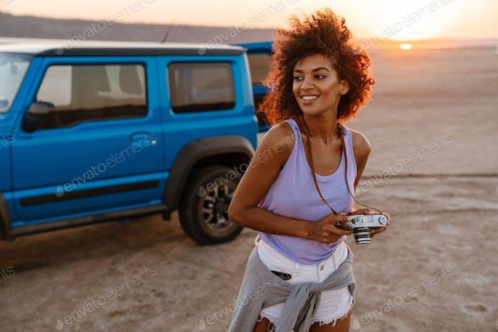Изображение афро-американской девушки держит ретро-камеру в пустыне