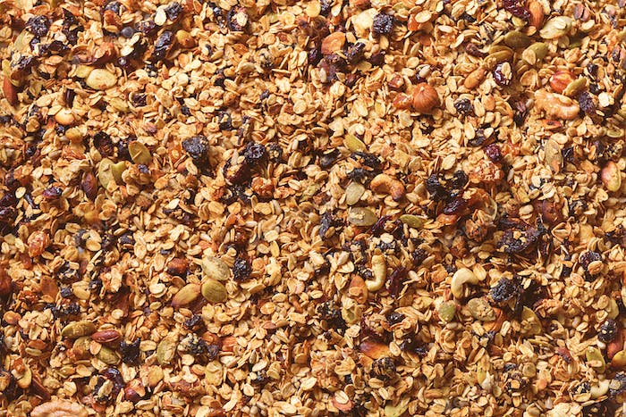 Organic homemade roasted granola with nuts and raisins on baking sheet. Food for breakfast. Meal