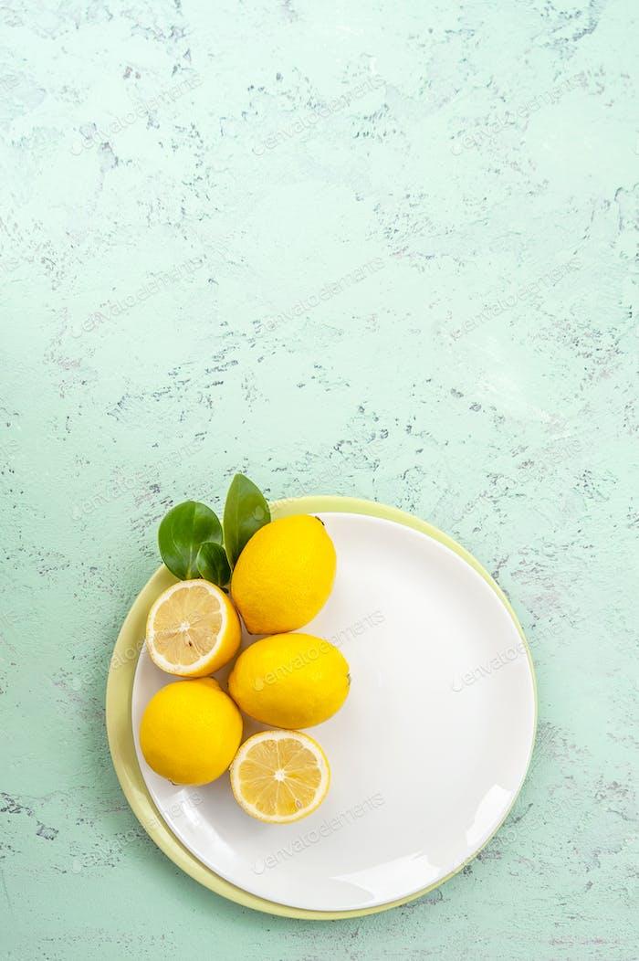 Ripe lemons on a plate on a mint-colored table. Flatt-barking.