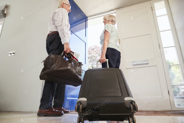 Senior couple with luggage leaving for a holiday, low angle