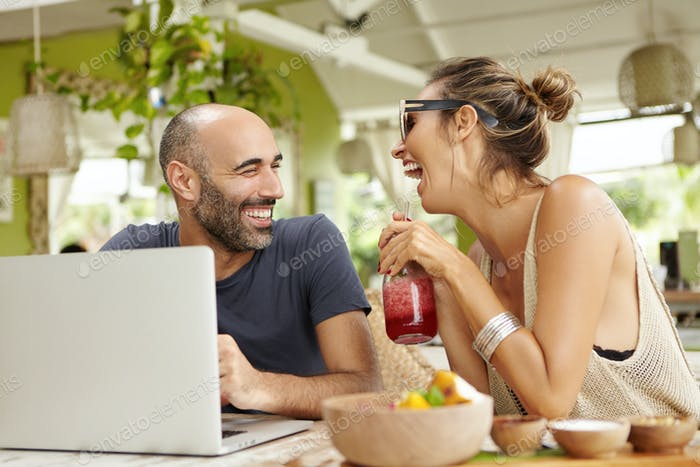 People, technology and lifestyle concept. Attractive bald man with beard sitting in front of laptop