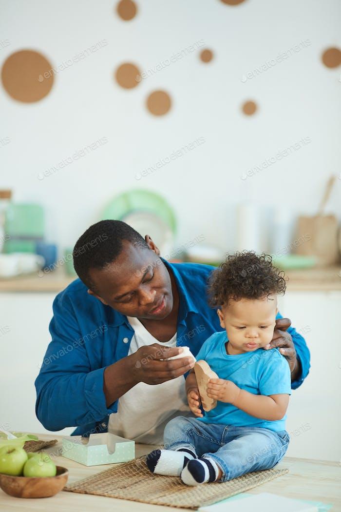 Caring Vater Fütterung Baby Sohn in Küche