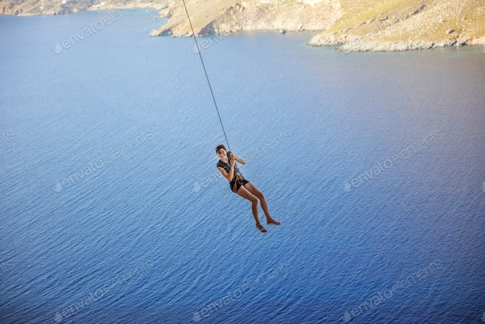 Young woman wearing safety harness swinging on rope