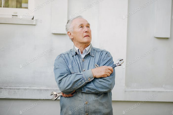 Old man standing near building with a repair tools