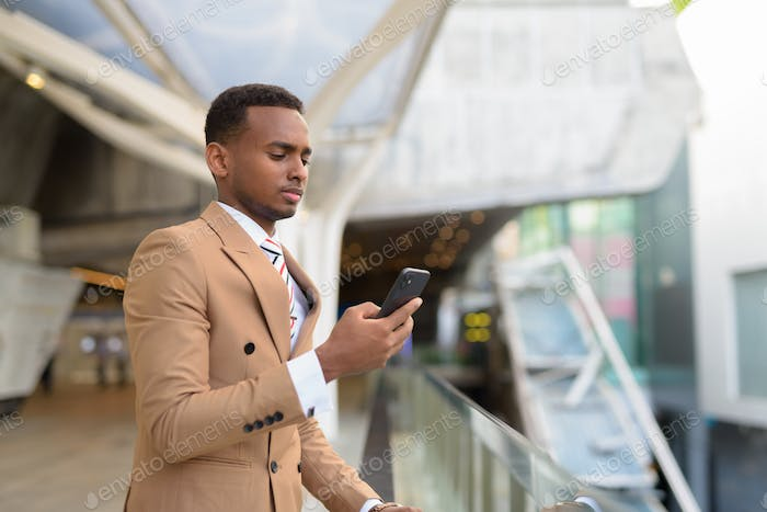 Young handsome African businessman using phone at footbridge in the city