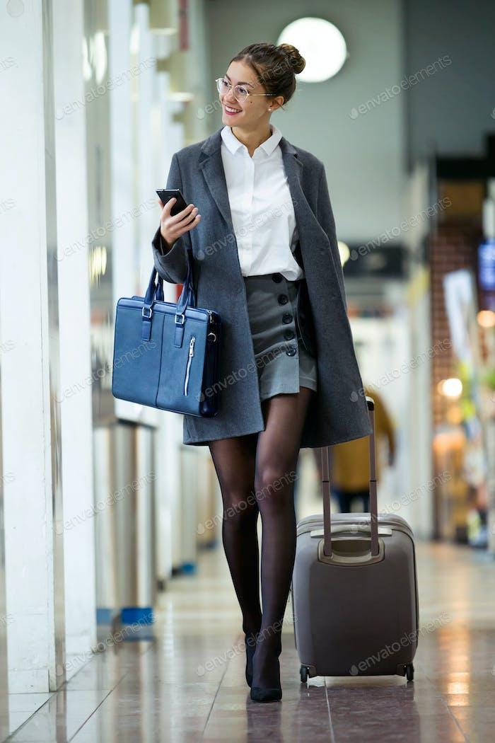 hermosa joven mujer de negocios caminando con maleta mientras holdin