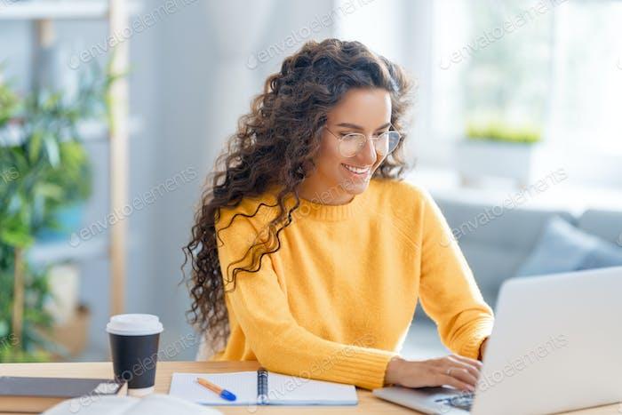 Frau arbeitet auf Laptop zu Hause.