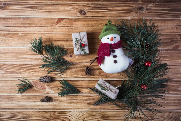 Christmas decorations on fir tree branches with gift boxes and snowman cookie on wooden table