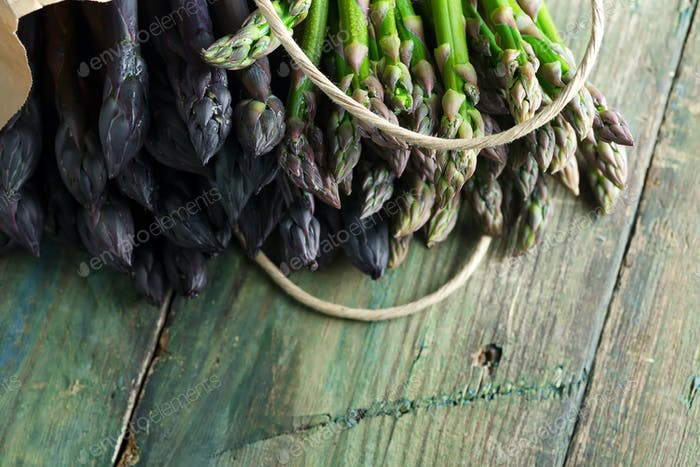 Paper bag with freshly picked raw organic natural purple asparagus spears on a wooden background