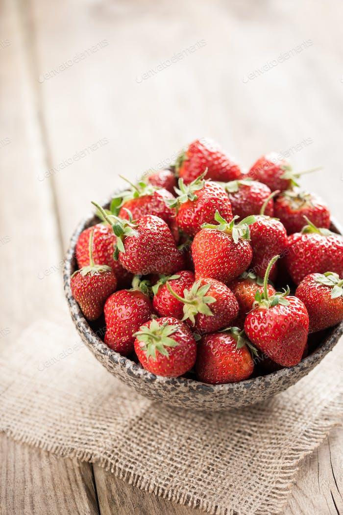 Red fresh strawberry in ceramic bowl