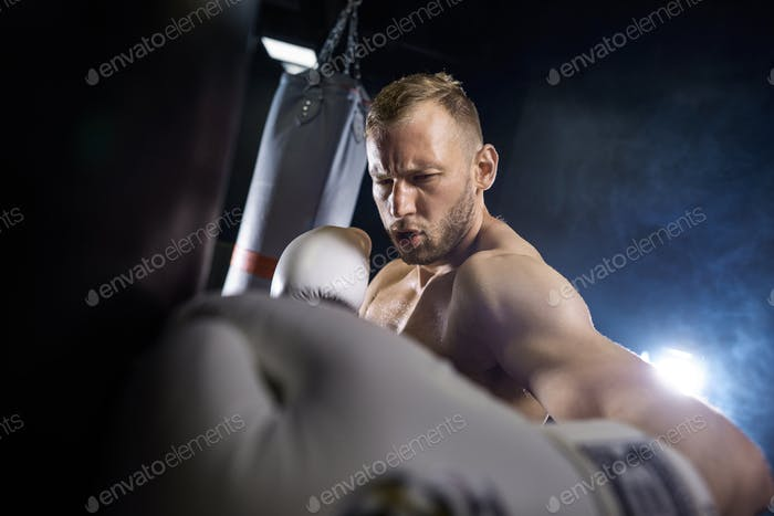 Mid adult boxer doing punching exercises