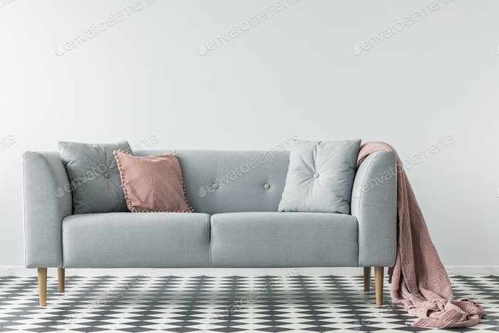 Pink blanket on grey couch with pillows on checkered floor in wh