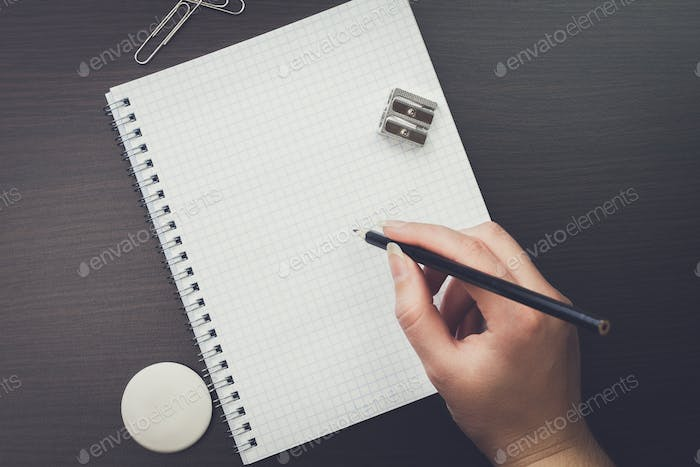 woman writing with pencil in the office