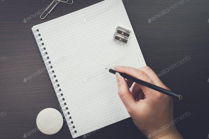 Frau Schreiben mit Bleistift im Büro
