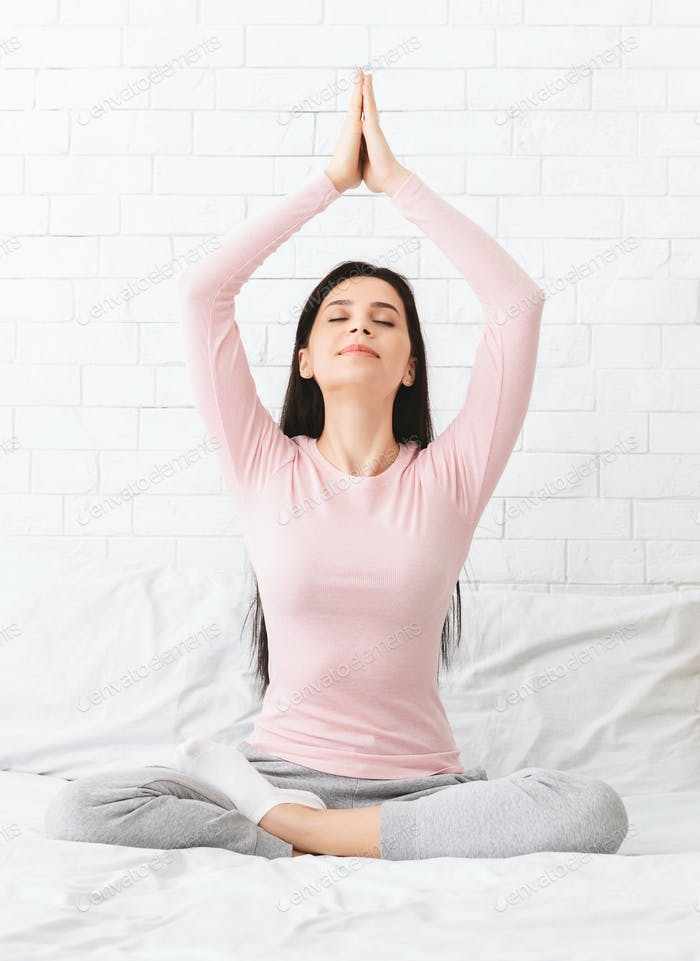 Peaceful woman meditating in bed at home