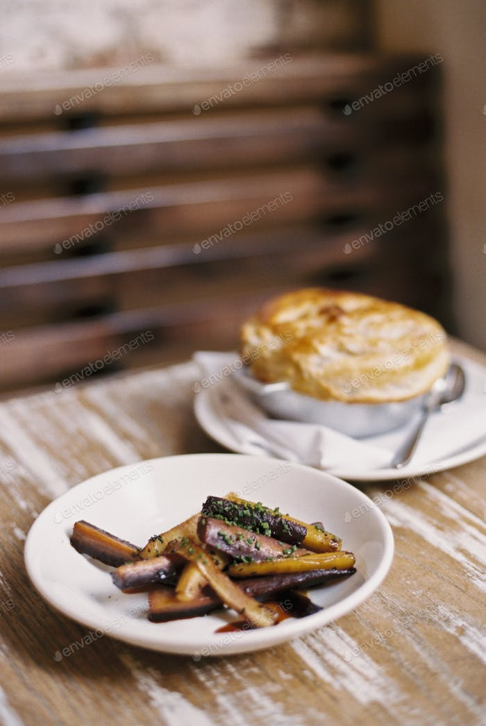 A plate of roasted vegetables cut into batons, and a pie on a tabletop.