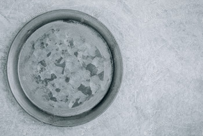 Empty round metal plate on gray concrete background, top view,