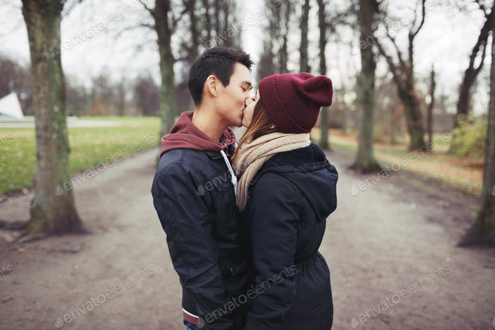 Teenage couple kissing outdoor in the park