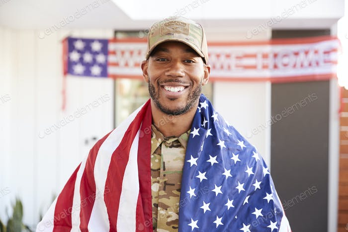 Millennial black soldier with US flag draped over his shoulders, smiling to camera, close up