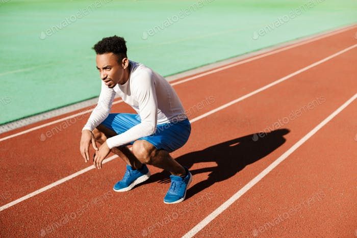 Young tired African American sportsman sit on one's haunches and resting after run at city stadium