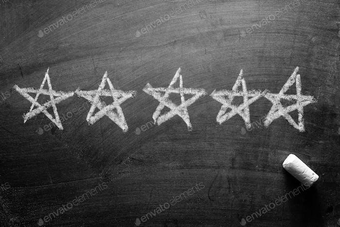 Línea de cinco estrellas dibujadas a mano en una pizarra