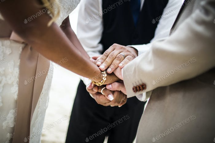 Close up of a husband and wife joining hands during the ceremony at a beach.