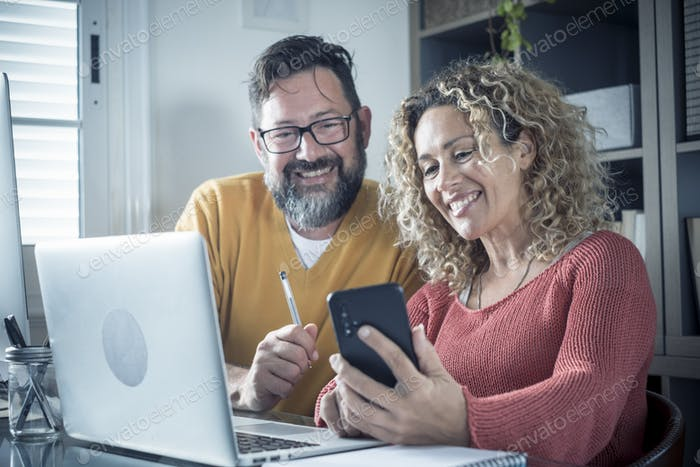 Man and woman team work together in couple at home with technology and online connection