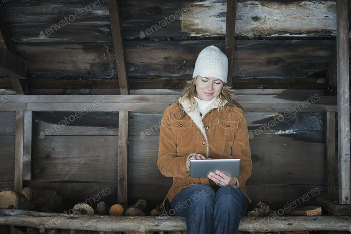 A woman sitting in an outbuilding in winter using a digital tablet.