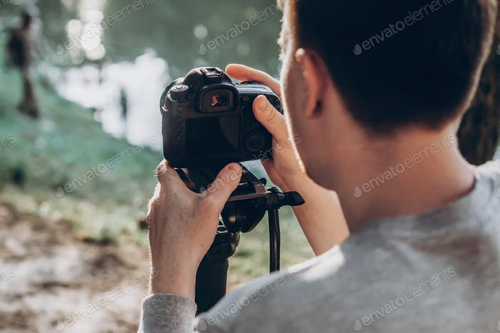 Man holding photo camera and filming footage