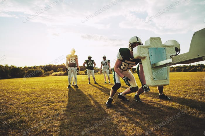 American football players practicing tackles on a sports field