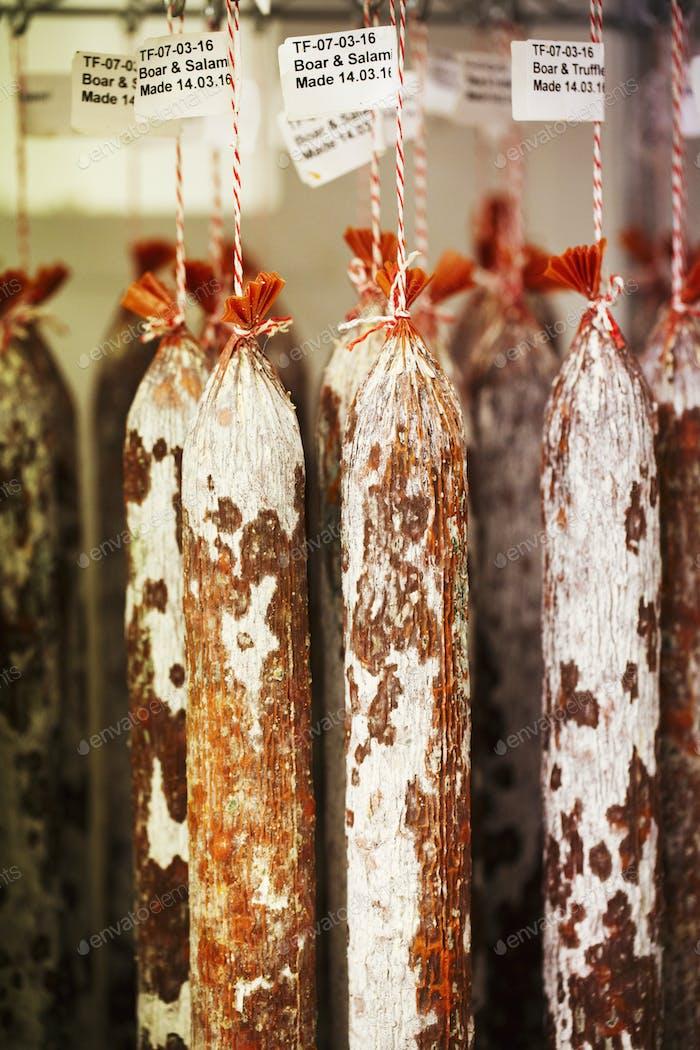 Nahaufnahme von Chorizo-Würstchen, die an Haken in einer Wurstwaren hängen.