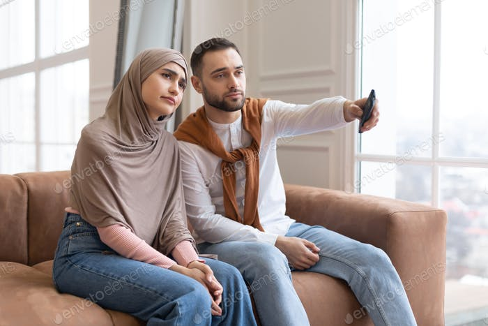 Bored Muslim Couple Watching Television Switching Channels Sitting At Home