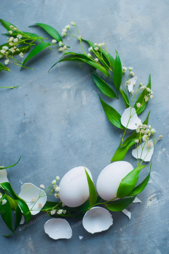 Circle vingette with white Easter eggs, decorative green leaves and spring flowers. Organic cooking